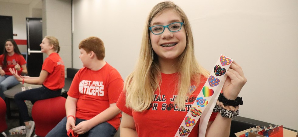 A St. Paul student smiles and shows a roll of stickers in red tshirt.